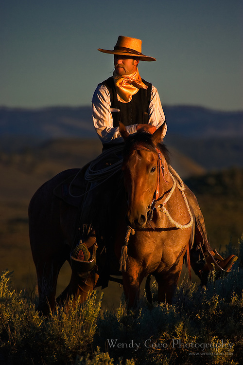 Wrangler on horseback gaszing at view at the end of the day.