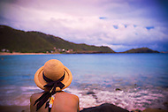 A woman in a pretty hat admires the view of the Caribbean Sea.