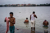 Men bathe on the banks of the Hooghly river near the Howrah Bridge in Kolkata, India, on Friday, May 26, 2017. Photographer: Sanjit Das