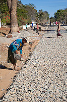 Myanmar, Burma, Shan State.  Laborer Building a Paved Road by Hand.  Laying Road Bed of Crushed Stones.