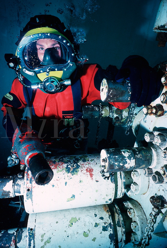 Commercial diver using underwater impact wrench working on underwater oil wellhead (deep sea diver)