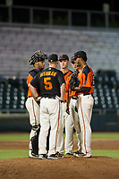AZL Giants pitching coach Glenn Dishman (5) visits with Jeffry Parra (5), Jacob Gonzalez (52), Nico Giarratano (9), and Olbis Parra (72) during a game against the AZL Brewers on August 15, 2017 at Scottsdale Stadium in Scottsdale, Arizona. AZL Giants defeated the AZL Brewers 4-3. (Zachary Lucy/Four Seam Images)