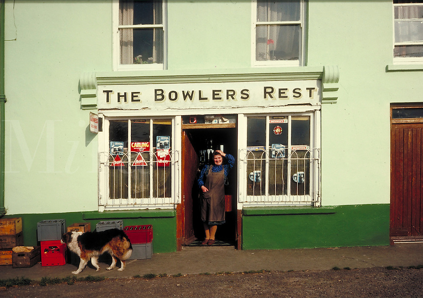 The exterior of the Bowler's Rest Pub, woman tavern keeper stands in the doorway as dog strolls by. occupations, female, street scene,. Ireland County Cork.