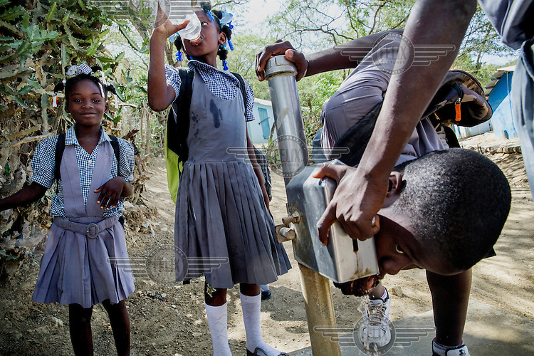 Pupils drink from a stand pipe in the playground of their school in the village Poste Metier. The water tap is protected by an inox plate so that the tap cannot be contaminated. It was constructed by the local NGO ODRINO.