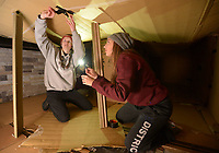 NWA Democrat-Gazette/ANDY SHUPE<br /> Grace Wood (left) and Kamilla Sarvestani, both senior members of the Fayetteville High School Student Countil, work together Thursday, Dec. 6, 2018, inside their cardboard structure to seal up its ceiling with duct tape during the 20th annual Homeless Vigil at the school. Students are spending the night outside to raise awareness and money for the district's Families in Transition Program which serves students and their families in need of assistance.