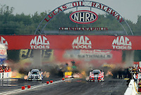 Sept. 1, 2012; Claremont, IN, USA: NHRA funny car driver Tony Pedregon (left) races alongside brother Cruz Pedregon during qualifying for the US Nationals at Lucas Oil Raceway. Mandatory Credit: Mark J. Rebilas-