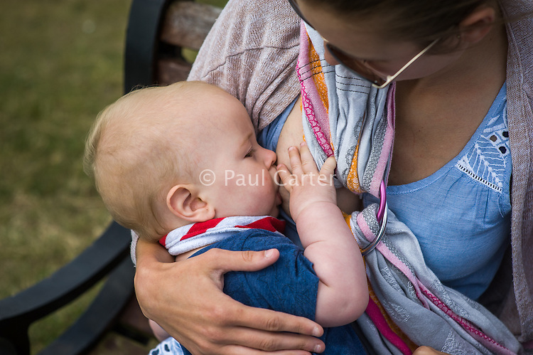 "A young mother breastfeeding her baby while sitting on a park bench.<br /> <br /> Image from the breastfeeding collection of the ""We Do It In Public"" documentary photography picture library project: <br />  www.breastfeedinginpublic.co.uk<br /> <br /> <br /> Dorset, England, UK<br /> 2015<br /> <br /> © Paul Carter / wdiip.co.uk"