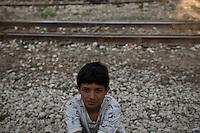 Grecia, Patrasso 2011: rifugiati afghani in un improvvisato campo in una stazione ferroviaria abbandonata. Ritratto di un ragazzino seduto. Dietro di lui i binari della stazione. Grece ville de Patras  2011 - refugies afghans dans une gare abandonnee