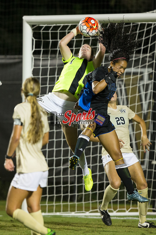 Lindsay Preston (1) of the Wake Forest Demon Deacons makes a save as Darian Jenkins (11) of the UCLA Bruins tries to head the ball during second half action at Spry Soccer Stadium on September 11, 2015 in Winston-Salem, North Carolina.  The Bruins defeated the Demon Deacons 2-1.  (Brian Westerholt/Sports On Film)