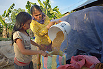 Lay Mao and her daughter gather rice that has been drying in the sun in the village of Dong in northern Cambodia.