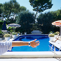 Designer Nicholas Alvis Vega holds out his arm showing a watch with a face in the same shade as the swimming pool at his house in the Cote d'Azur