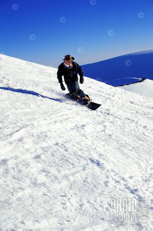 Front view of snowboarder descending the slopes of Mauna Kea with snow covered cinder cone and vivid blue sky in background.