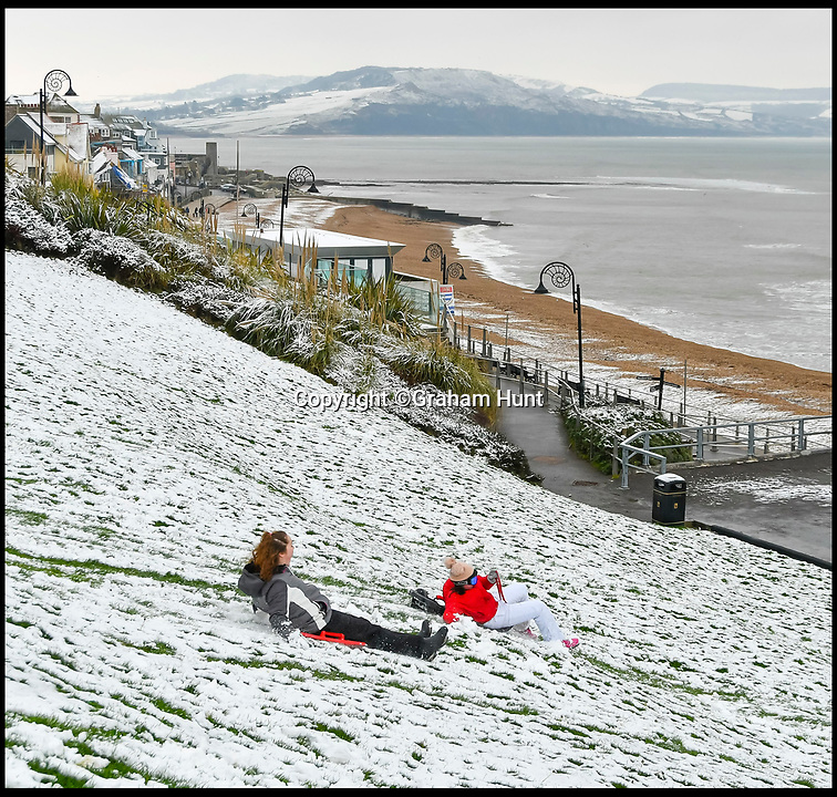BNPS.co.uk (01202 558833)<br /> Pic: Graham Hunt/BNPS<br /> <br /> The seaside resort of Lyme Regis in Dorset looking wintery after heavy overnight snow covered southern Britain.<br /> <br /> Teenagers having fun sledging down a steep slope in Lister Gardens.