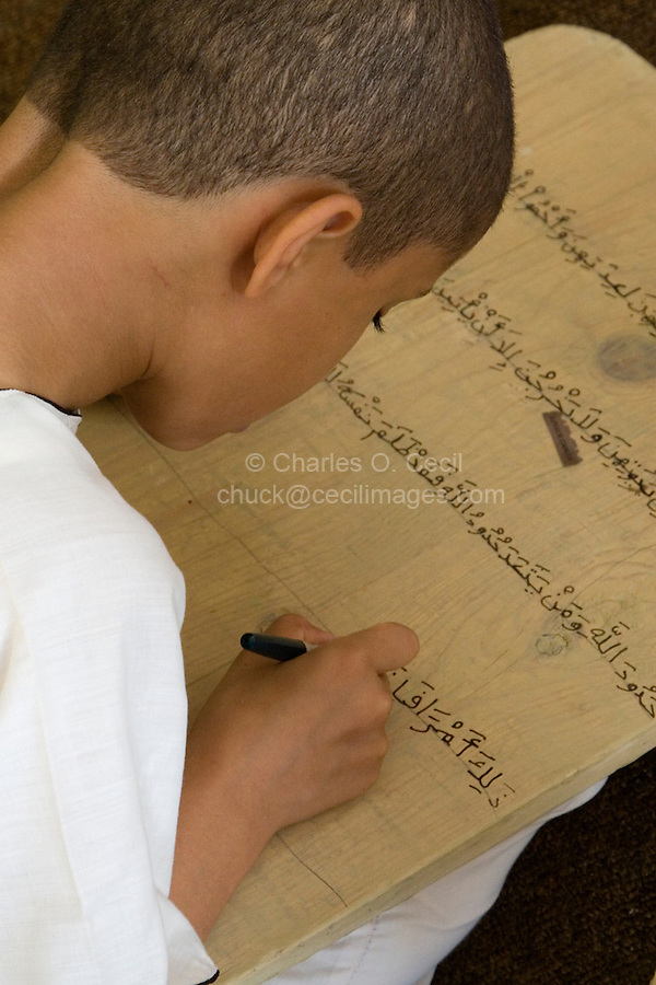 Zliten, Libya. Boy Writes Verses from the Koran on his Prayer Board.  He studies to memorize the Koran, working under the supervision of a teacher, or muqri.