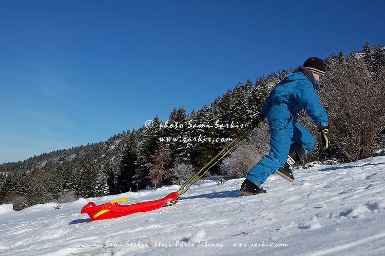 Boy towing a sled uphill in the snow, Lans-en-Vercors, Isère, France.