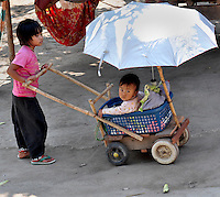 An innovative stroller being pushed by the child's sister as seen in a tribal village in Thailand. An example of simplicity, creativity and thinking out of the box.