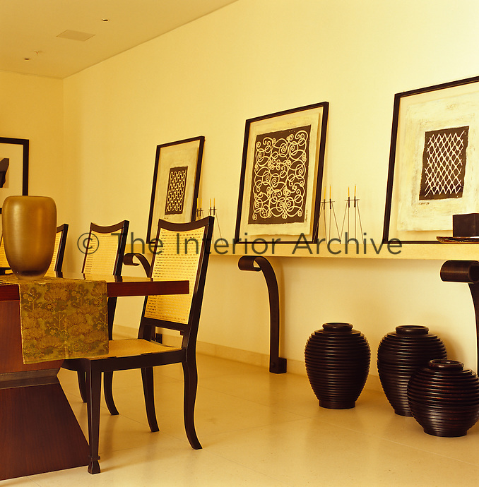 A series of framed black and white paintings displayed on a large wall shelf supported by legs in the dining area