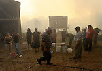 Porqueira´s neighbors are seen around with a bucket near fires in Porqueira, August 14, 2010, near A Coruña. Pedro ARMESTRE