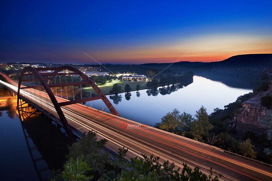 A colorful Sunset falls on the Austin Loop 360 Pennybacker Bridge as it spans over Lake Austin in Austin Texas
