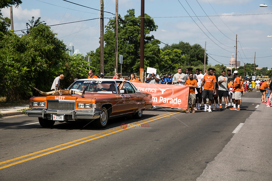 """AUSTIN, TEXAS - A vintage cadillac painted in """"burnt orange"""" with longhorns mounted on the hood drives along the University of Texas Athletics Department at the 2016 Central Texas Juneteenth Celebration Parade on on Sat. June 18, 2016. <br /> <br /> Use of this image in advertising or for promotional purposes is prohibited.<br /> <br /> Editorial Credit: Dan Herron / Herronstock Editorial."""