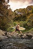 USA, Hawaii, The Big Island, a surfer hops across the Honoli'i river on his way to the beach, North of Hilo