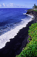 The beautiful black sand of Kehena beach on the Big Island of Hawaii is starkly contrasted by the white foam rolling in off the blue Pacific Ocean.