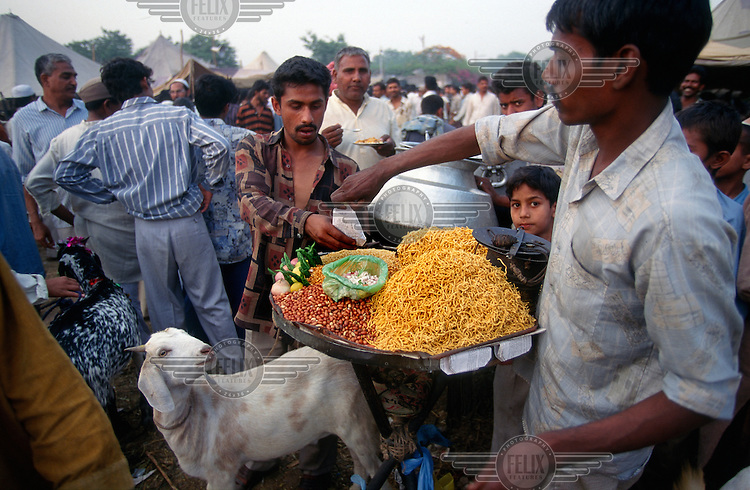 Snack seller at work in the annual muslim market beside the Jama Masjid mosque during the festival of Eid, when thousands of goats will be slaughtered.