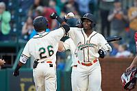 Lolo Sanchez (26) of the Greensboro Grasshoppers bumps arms with teammate Rodolfo Castro (7) after hitting a three-run home run against the Hagerstown Suns at First National Bank Field on April 6, 2019 in Greensboro, North Carolina. The Suns defeated the Grasshoppers 6-5. (Brian Westerholt/Four Seam Images)
