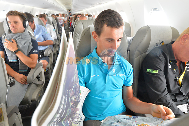 Alexis VUILLERMOZ (FRA) AG2R catches up with the latest news on board the plane to take the teams to the start of Stage 21 of the 2015 Tour de France running 109.5km from Sevres to Paris - Champs Elysees, France. 26th July 2015.<br /> Photo: ASO/B.Bade/Newsfile