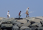 People walking out on the North Jetty at the Manasquan Inlet to do some fishing.