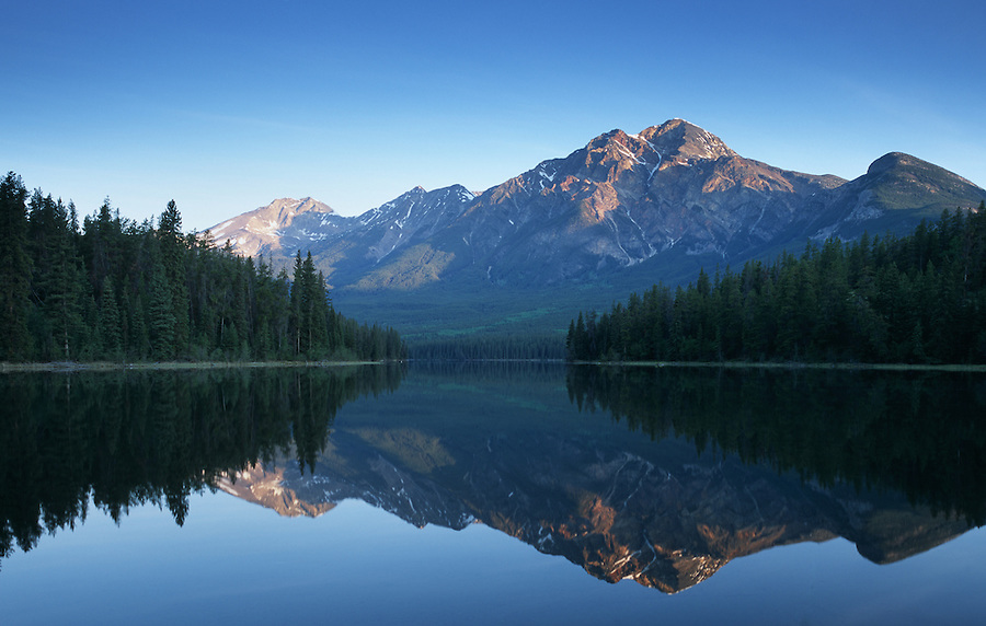 The air and water are perfectly still on an early morning along Pyramid Lake, reflecting Pyramid Mountain in the background in the Jasper National Park area of Alberta Canada.
