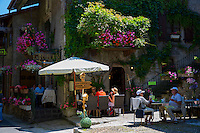 Diners at restaurant cafe La Raboue in the historic medieval district of Yvoire by Lac Leman, Lake Geneva, France