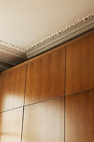 The simple hand-made cupboards are of grained oak and make a pleasing contrast to the ornate stucco of the ceiling