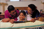 father and mother reading to their daughter on bed