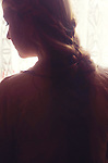 Headshot of young woman seen in profile with hair in plait