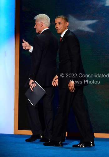 Former United States President Bill Clinton gives a thumbs-up as he and U.S. President Barack Obama leave the podium following Clinton's remarks at the 2012 Democratic National Convention in Charlotte, North Carolina on Wednesday, September 5, 2012.  .Credit: Ron Sachs / CNP.(RESTRICTION: NO New York or New Jersey Newspapers or newspapers within a 75 mile radius of New York City)