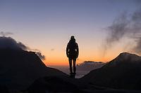 Silhouette of female hiker looking over 3:00am dawn twilight in late summer, Moskenesøy, Lofoten Islands, Norway