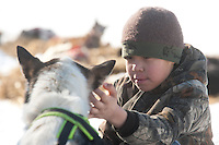 Bradley Kruger pets one of Hugh Neff's dogs in the Anvik checkpoint on Friday.