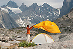 A young man sets up his tent in Titcomb Basin, Wind River Mountains, Wyoming.