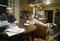 10-year-old Michael O'Reilly-Birtcher, center, pets his dog Alaska while having breakfast with his adoptive parents Thom O'Reilly, left, and Harold Birtcher in their home Thursday, Feb. 16, 2006, in Upper Arlington, Ohio. Because same-sex partners are barred from joint adoption in Ohio, O?Reilly and Birtcher, who have been together for 25 years, went to Oregon three years ago to jointly adopt Michael. A bill introduced in the Ohio Legislature this month would bar all gays and lesbians from adoptions and foster care.<br />