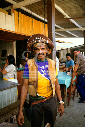 Brazil. Man dressed in Cangaceiro style with typical hat, with t-shirt using Brazilian flag motif.