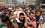 Palestinian mourners carry the body of Yasser Habib, 24, who died of his wounds endured during clashes with Israeli troops in a tent city protest where Palestinians demand the right to return to their homeland at the Israel-Gaza border, during his funeral in Gaza city, on May 26, 2018. Photo by Mahmoud Ajour