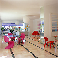 The main living area is furnished with pink Verner Panton chairs surrounding a bicycle-wheel 'touring table' by Gae Aulenti with a 1970's swivel chair in the corner