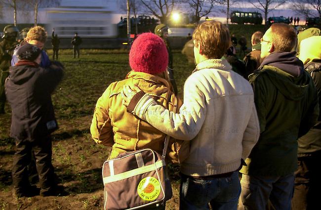 Proteste gegen Castor-Transport<br /> Ein Transport von zwoelf Castoren aus der franzoesichen Wiederaufbereitungsanlage La Hague wurde am Donnerstag den 14. November 2002 per LKW von Dannenberg nach Gorleben gebracht. In der Nacht vor dem Transport versuchten ca. 1.000 Menschen mit einer Strassenblockade einen letzten Versuch den Transport zu stoppen. Sie wurden jedoch von Polizei und Bundesgrenzschutz von der Strasse getragen und auf einem Feld eingekesselt.<br /> Der Transport des Atommuell lief ab morgens um 6.27 Uhr von Dannenberg in das sogenannte Zwischenlager bei Gorleben reibungslos.<br /> Hier: Atomkraftgegener beobachten vor einer Polizeiabsperrung die Vorbeifahrt des Castor-Tranport.<br /> 14.11.2002, Laase / Niedersachsen<br /> Copyright: Christian-Ditsch.de<br /> [Inhaltsveraendernde Manipulation des Fotos nur nach ausdruecklicher Genehmigung des Fotografen. Vereinbarungen ueber Abtretung von Persoenlichkeitsrechten/Model Release der abgebildeten Person/Personen liegen nicht vor. NO MODEL RELEASE! Nur fuer Redaktionelle Zwecke. Don't publish without copyright Christian-Ditsch.de, Veroeffentlichung nur mit Fotografennennung, sowie gegen Honorar, MwSt. und Beleg. Konto: I N G - D i B a, IBAN DE58500105175400192269, BIC INGDDEFFXXX, Kontakt: post@christian-ditsch.de<br /> Bei der Bearbeitung der Dateiinformationen darf die Urheberkennzeichnung in den EXIF- und  IPTC-Daten nicht entfernt werden, diese sind in digitalen Medien nach &sect;95c UrhG rechtlich geschuetzt. Der Urhebervermerk wird gemaess &sect;13 UrhG verlangt.]