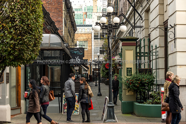 10/24/2015 &mdash; Victoria, British Columbia, Canada<br /> <br /> Trounce Alley, seen here from the entrance at Government street, is a discrete passage connecting two main thoroughfares in downtown Victoria, British Columbia. It has a long history as a commercial strip, albeit a tiny one. It goes back to the mid-1800s when developer and architect Thomas Trounce designed the lane to provide easy access to stores he owned. With fluctuations in the economy, businesses have come and gone over time, but today, still lined with 125-year-old gaslights, the corridor is a diverse micro hub where old-world businesses coexist alongside hip new shops and restaurants, none of which disrupt the pathway&rsquo;s quaint charm.<br /> <br /> <br /> Photograph by Stuart Isett<br /> &copy;2015 Stuart Isett. All rights reserved.