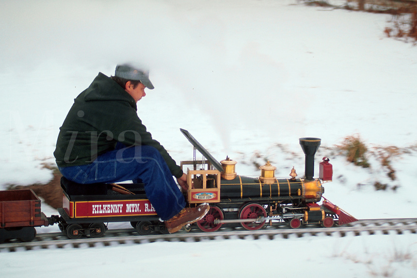 Model railroading - Man sits on a model train as it rides along tracks outdoors.