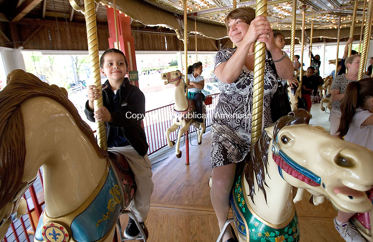 MIDDLEBURY, CT. 12 May 2011-051211SV05--Eric Ligo, 5, a kindergartener of Brooklyn Elementary School takes a rid with principal Dr. Patty Frageau on the merry go round at Quassy Amusement Park in Middlebury Friday. Hundreds&nbsp;of Waterbury students went to Quassy Amusement Park as a reward for good behavior.<br /> Steven Valenti Republican-American
