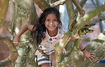 A girl climbs a tree in the Nacoes Indigenas neighborhood in Manaus, Brazil. The neighborhood is home to members of more than a dozen indigenous groups, many of whose members have migrated to the city in recent years from their homes in the Amazon forest.