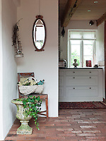 The floor of the entrance hall and adjoining kitchen is laid with handmade bricks, while a restored 19th century chair and second hand mirror create a pretty feature in the corner