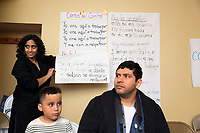 (171126RREI2161) Many Languages One Voice,  MLOV,  Holiday Celebration and Immigrant Legal Rights Workshop in La Casa, Mt. Pleasant. MLOV is on the same block as La Esquina where Latinos have gathered for decades at the corner of Mt. Pleasant St. and Kenyon St. NW. to play chekers (damas). MLOV Exec. Dir. Sapna Pandya, (with list) Washington DC.  Nov. 26 ,2017 . ©  Rick Reinhard  2017     email   rick@rickreinhard.com